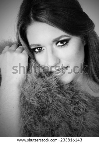 close up black and White portrait of a Young sensual beautiful girl posing with fur coat close to her Young perfect skin - stock photo
