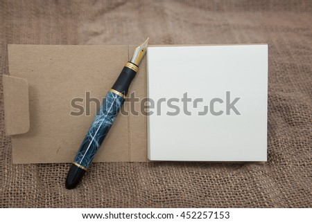 Close-up blank sheet of note and fountain pen on brown cotton, for text and background, Fountain Chinese Style pens for Writing Good Study Writing Tools - stock photo