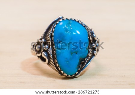 close up blue stone in silver ring on wood background - stock photo