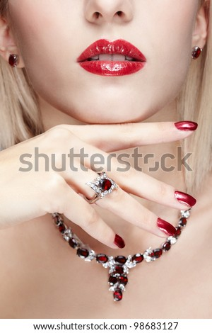 close-up body part portrait of beautiful woman with healthy skin, red manicure and jewellery - stock photo