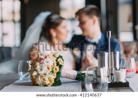 Close-up bouquet of roses on set wedding table with bride and groom in the background - stock photo