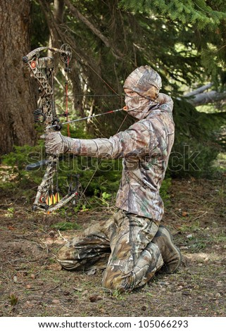 close-up bow hunter dressed in camouflage pulling bow back in woods - stock photo