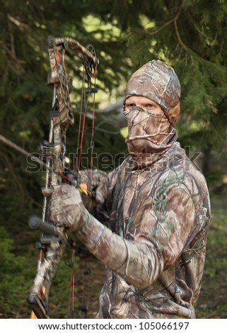 close-up bow hunter dressed in camouflage ready for a shot - stock photo