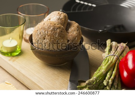 Close up Brown Bread on Bowl on Top of Wooden Board with Candles on Glasses and Cutting Knife - stock photo