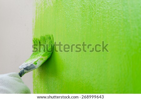 Close up brush painting green color on wall - green coloring - stock photo