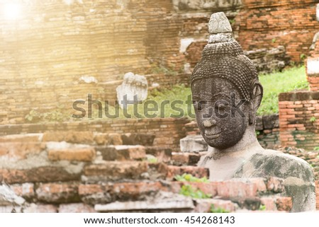 Close up Buddha image look through blurry focus brick wall with lens flare effect sunlight and blurred background. Selective focus on Buddha statue. - stock photo