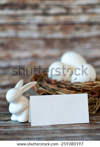 Close up Bunny Porcelain and Chicken Eggs in Nest with Blank Note Paper on Top of Wooden Table, Emphasizing Copy Space. - stock photo