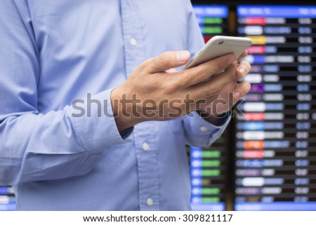 close up business man checking stock market by smart phone over blurred stock board.economics concept.business concept. - stock photo