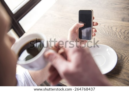 Close-up. Businessman drinking a coffee and looking in phone in restaurant. - stock photo