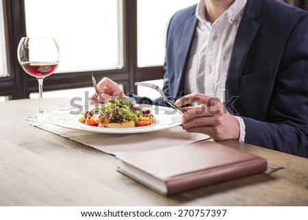 Close-up. Businessman eating during a business lunch in restaurant. - stock photo