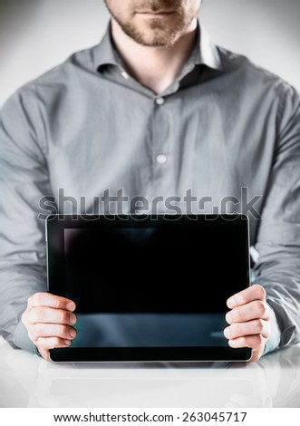 Close up Businessman in Long Sleeves Shirt Holding Powered Off Tablet Computer and Showing the Screen at the Camera, Emphasizing Copy Space. - stock photo