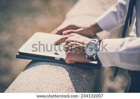 close up businessman man hand using tablet device outdoor - stock photo