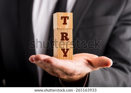 Close up Businessman Showing Conceptual Piled Wooden Cubes with TRY Word on his Bare Palm. - stock photo