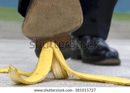 Close up businessman stepping on banana skin peel - stock photo