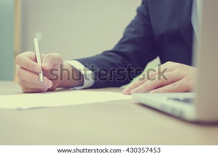 close up businessman writing on paper and typing on laptop computer desk in office room:busy business man thinking and note on paperwork:businessman sign his signature:vintage mood tone color effect. - stock photo