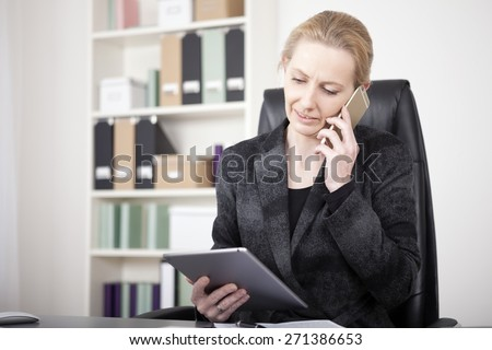 Close up Businesswoman in Black Suit Holding a Tablet Device While Calling to Someone on Mobile Phone. - stock photo