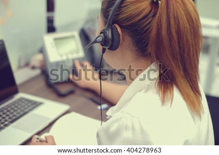 close up call centre woman working office room:focus on headphone asian girl response answer customer's question or partner concept:people with technology personalization:vintage filter effect.hotline - stock photo