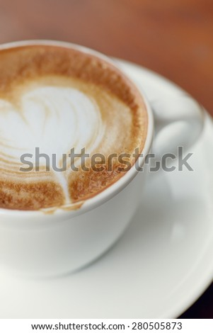 Close up cappuccino coffee cup on the wood table - stock photo