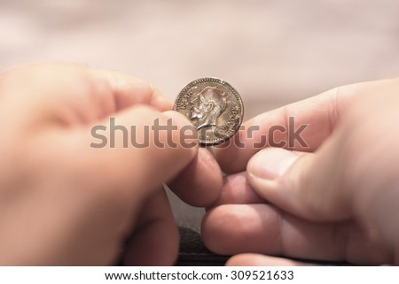Close up capture of an Caucasian man hands holding and old greek new years cake coin showing king face - stock photo