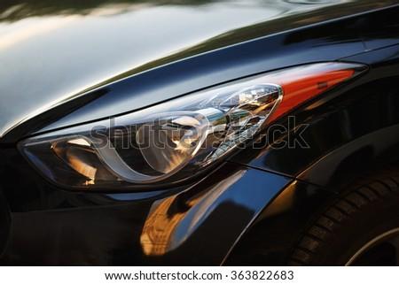 Close-up car headlight of powerful modern black car with glare. - stock photo