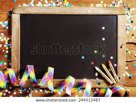 Close up Carnival Black Board, Decorated with Confetti, with Copy Space on Wooden Background. - stock photo