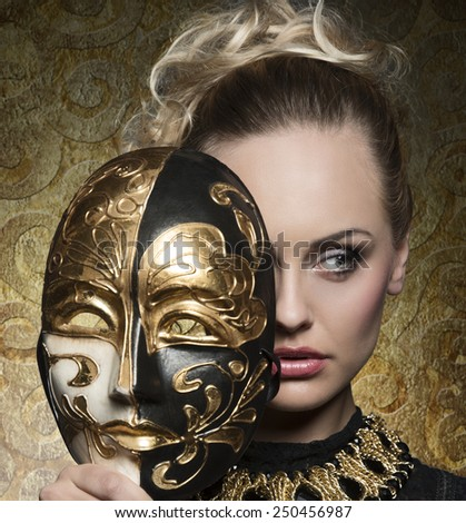 close-up carnival portrait of very beautiful blonde woman with baroque mask in the hands and antique precious jewellery  - stock photo