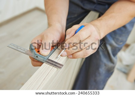 Close-up carpenter process of wood door marking for locksmith installation - stock photo