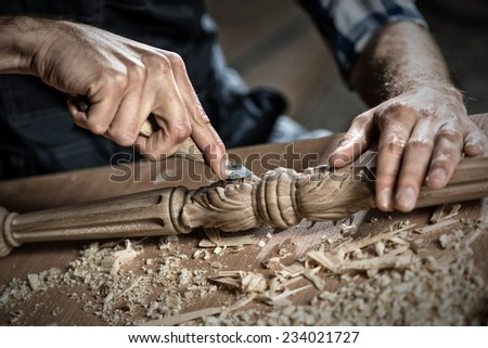 Close up carpenter's hands that work with cutter - stock photo
