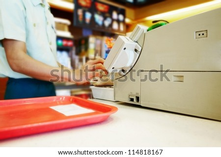Close up cash desk with mans hand and tray in the fast food - stock photo