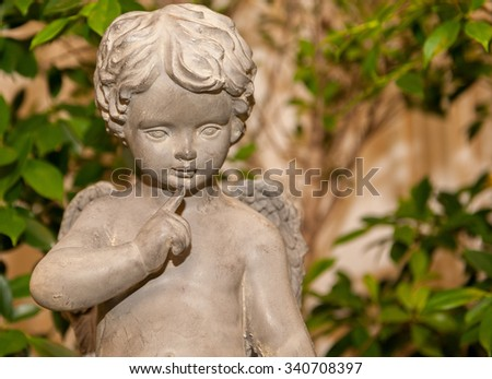 close up cement cherub doll in garden - stock photo