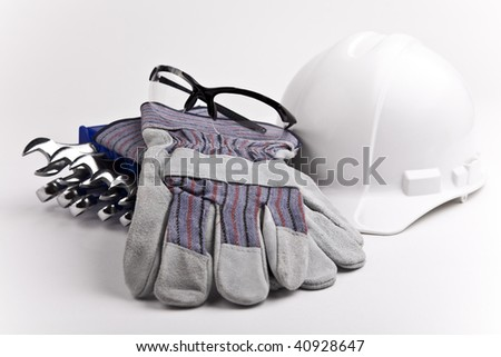 close up  centered wrenches hard hat leather gloves safety glasses PPE - stock photo