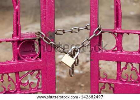Close up chain locked on pink color fence gate - stock photo