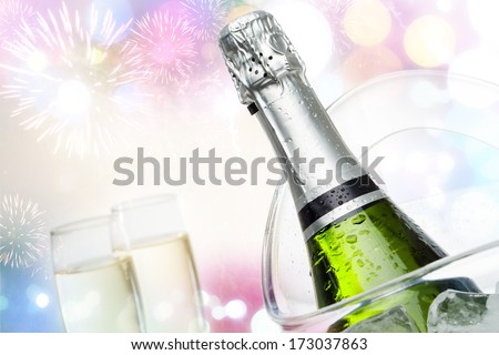 Close up champagne bottle in ice bucket with festive colorful background. - stock photo