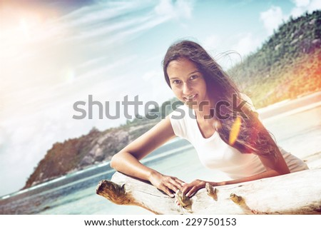 Close up Charming Young Woman Sitting Beside Dry Tree Branch at the Beach Illuminated with Sunlight. - stock photo
