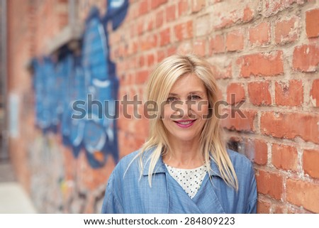 Close up Cheerful Blond Adult Woman Leaning on Brick Outside Wall of a Building and Looking at the Camera. - stock photo