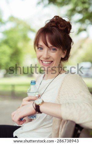 Close up Cheerful Young Attractive Woman at the Bench Holding a Bottle of Water While Looking at the Camera with Toothy Smile. - stock photo