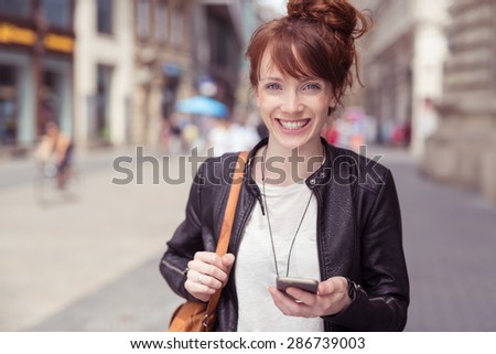 Close up Cheerful Young Lady in Trendy Outfit, Holding her Mobile Phone While Walking at the City Street and Looking at the Camera. - stock photo