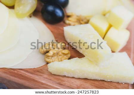 close up cheese plate with grapes on the wooden table - stock photo