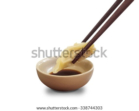 Close up chopsticks pinch fresh boiled dumplings to dipping sauce on white with clipping path - stock photo