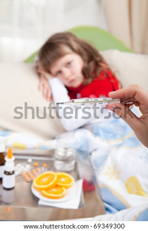 Close-up clinical thermometer in woman hand showing fever and little sick girl wrapped in red scarf under blanket in the bed and tray with pills, sprays, oranges and glass of water - stock photo