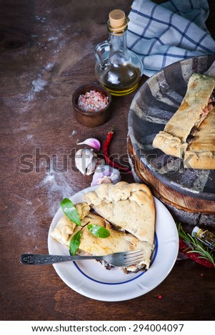 Close-up closed italian pizza calzone on the wood table - stock photo