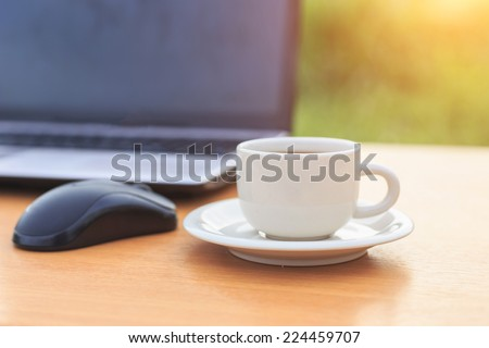 Close up coffee cup and laptop on the table in the morning - stock photo