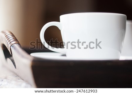 Close up coffee cup in wooden tray - stock photo