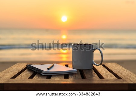Close up coffee cup on wood table at sunset or sunrise beach - stock photo