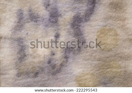 Close up color image of a felted, wool, eco paper technique on hand made material using leaves and natural substances for the color and design. Can be used for background or added texture. - stock photo