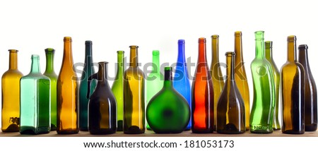 close-up colorful dusty bottles in various shapes standing on a wooden board in a studio on background white soft light - stock photo