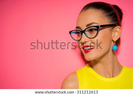 Close up colorful studio portrait of pretty young woman in glasses with red lipstick makeup. - stock photo