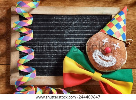 Close up Conceptual Carnival Donuts, Decorated with Hat, Ribbon and Confetti, with Black Board at the Back. Placed on Wooden Table. Emphasizing Copy Space for Texts. - stock photo