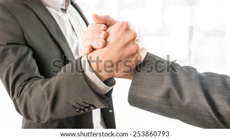 Close up Conceptual Two Businessmen in Gray Business Suit Gripping Their Hands at the Office. - stock photo