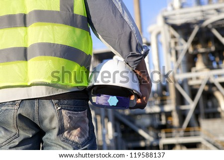 Close-up construction worker holding hardhat on location site - stock photo